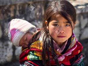 Sapa, Lao Cai Province, Vietnam - February 16, 2014: Unidentified Hmong girl carrying baby and wearing traditional attire in Sapa town on February 16, 2014, Lao Cai Province, North Vietnam.